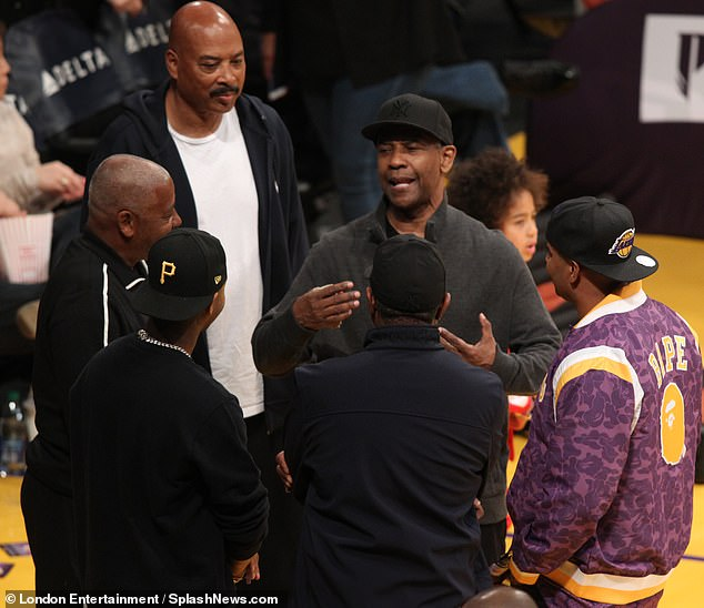 Chatty: The star looked delighted as he chatted with friends before taking his place courtside