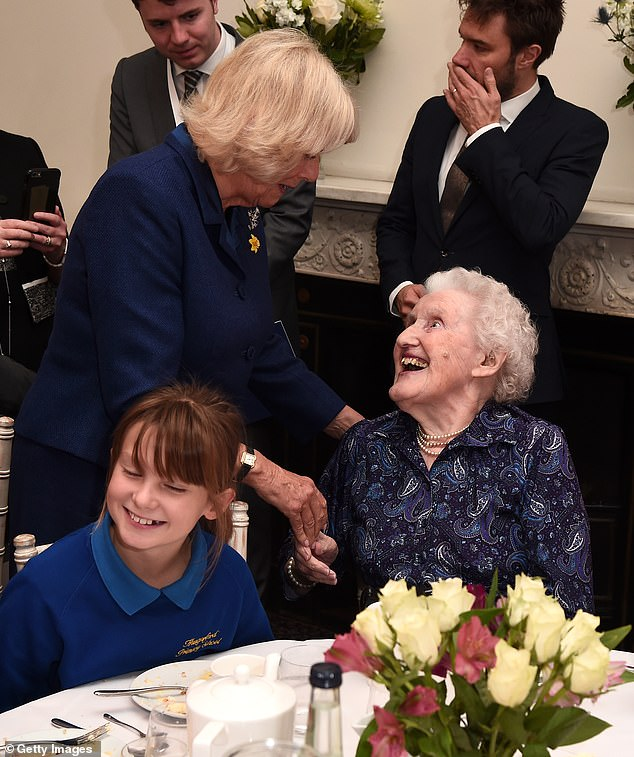 Camilla, 73, was seen sharing a joke with a local care home resident during a tea party at Eaton Square Upper School in London today