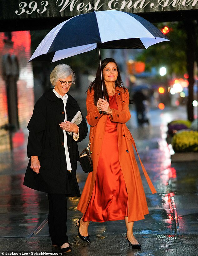 Movers and shakers:Katie could also be spotted sheltering beneath an umbrella with her mother as the pair of them pounded the pavement outside the event