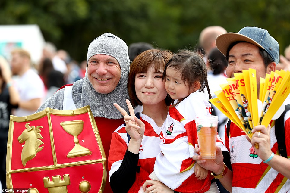 England fans dressed as St George mix with locals in Oita ahead of the game which pit two old rivals against each other