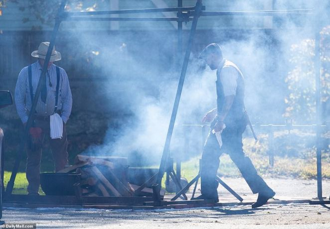 A caterer walks through wafting smoke as he continues to prepare for the Saturday wedding