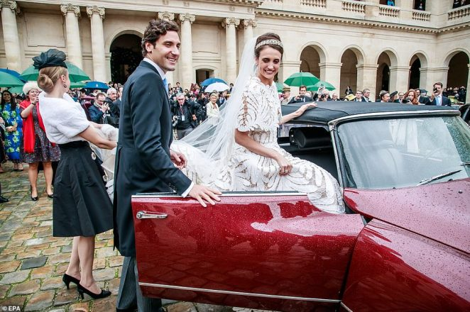 The couple leave the cathedral in a red convertible. The Prince opens the door for his bride as her sister carries her train into the car