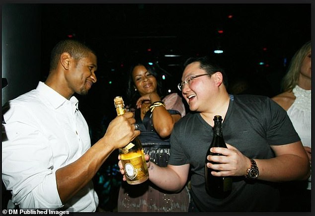 The financier is pictured drinking champagne with rapper Usher. Leach estimated that his lavish birthday event 'must have cost 100 billion dollars'