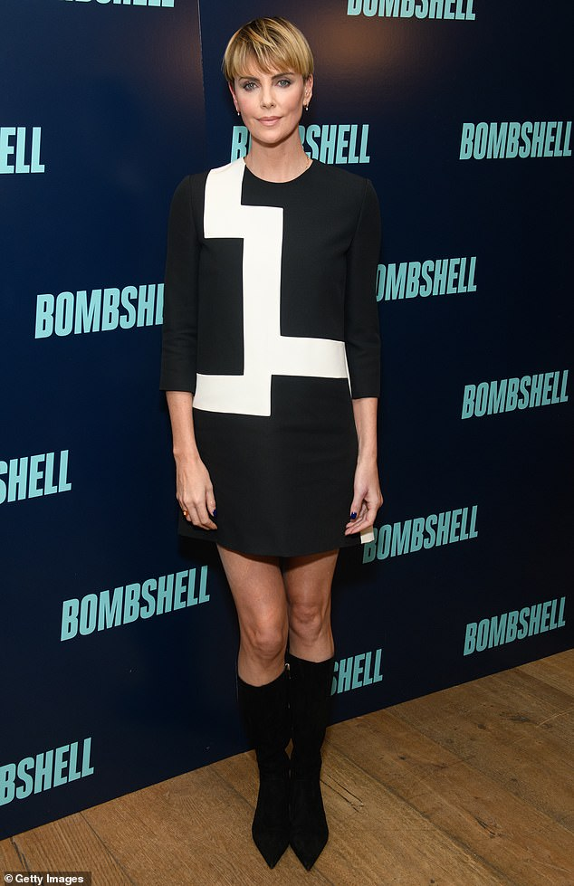 Retro vibes: Theron completed the '60s motif with a pair of pointed knee-length black stiletto boots