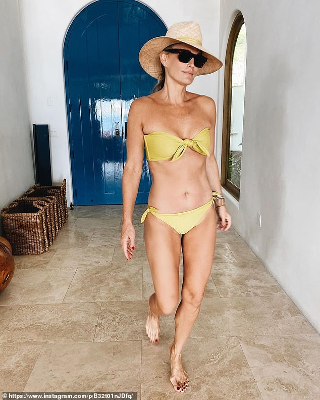 Beach babe! Sims worked a mustard yellow bathing suit and wide-brim hat during her trip