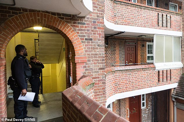 Police officers guard the scene in Deptford, South East London, today as the probe continues