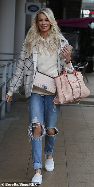 Eye-catching style: Toting a pair of Chanel bags, the reality star wore her blonde locks in voluminous waves, while she highlighted her good looks with a rich palette of makeup