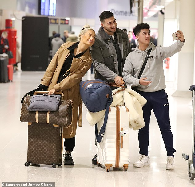 In demand:The couple carried their suitcases through the airport and also stopped to take a selfie with a fan before making their way home