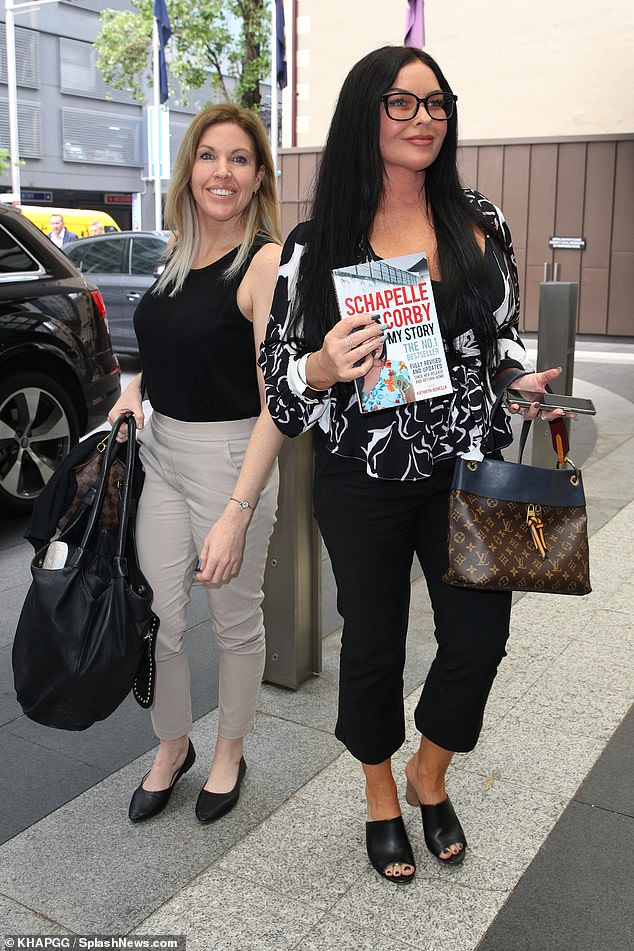 Launch party: Schapelle (right) made sure her re-revised autobiography was on full display as she arrived at the event alongside her sister, Mercedes Corby (left)