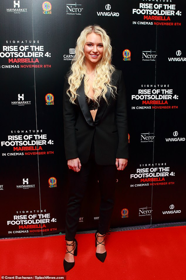 Glam: The surfer put on an incredibly busty display in a plunging black trouser suit which she teamed with a lacy bra