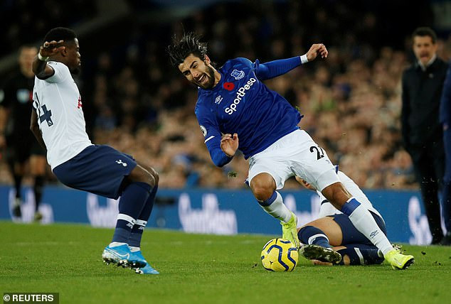 Gomes falls to the fall in pain before Serge Aurier (left) runs in to get the ball off the midfielder