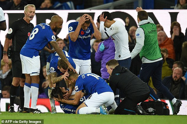 Players from both sides are in shock as Gomes receives urgent medical attention