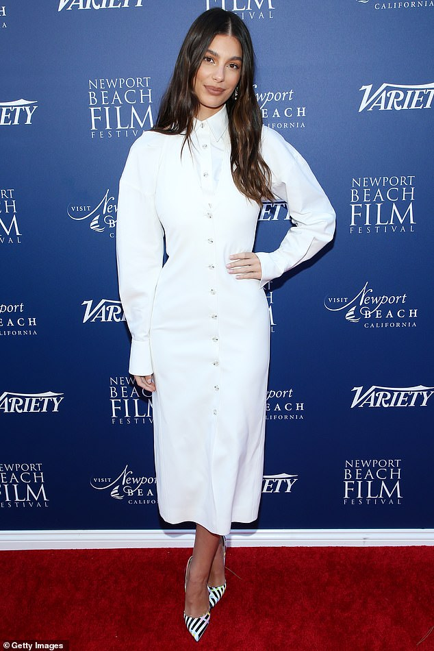 Chic display: The 22-year-old donned a slim white long-sleeve dress with lapels, cuffs and buttons down the front like a dress shirt