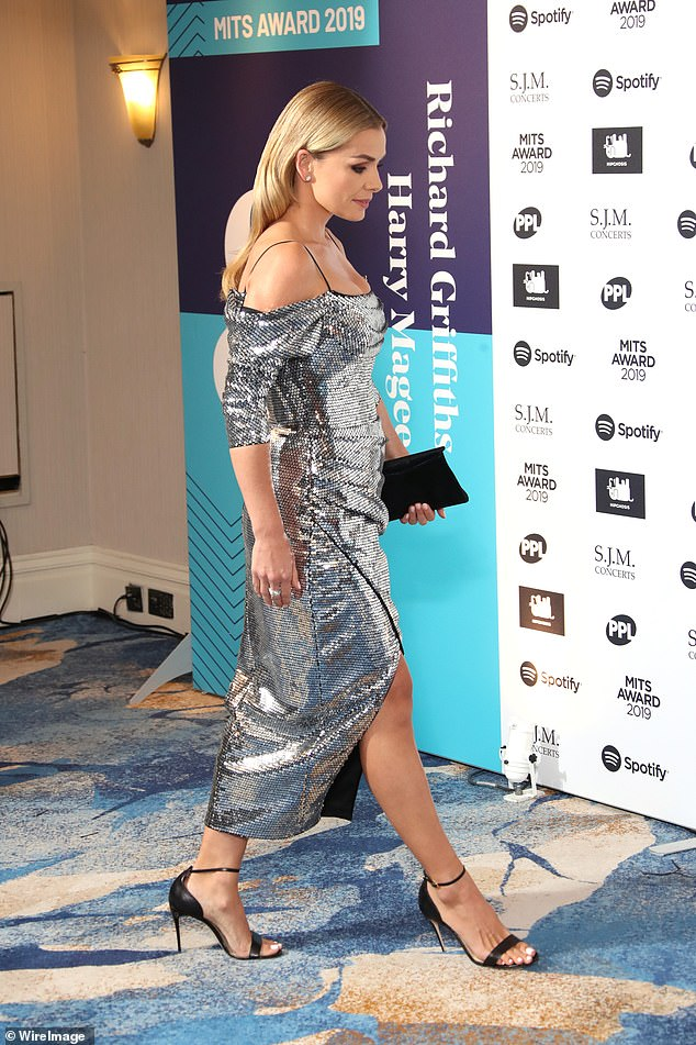 Fantastic: She toted her belongings in a chic black clutch while posing away in towering black heels