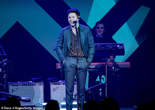 Happy: Niall looked in high spirits as he sang with his hands in his suit trousers' pockets