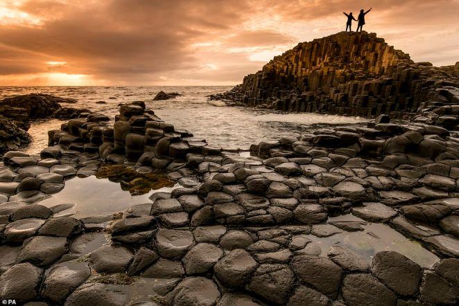Northern Ireland's world famous Giant's Causeway also made the final cut, with this image taken byGlenn Miles showing two people waving from the hexagonal rocks