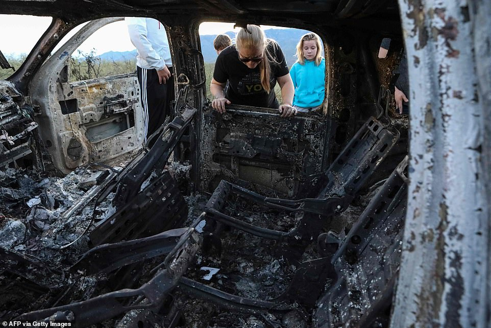 Emotional members of the LeBaron family look into the burned SUV where some of the nine murdered family members were killed and burned during a cartel gunmen ambush on Monday