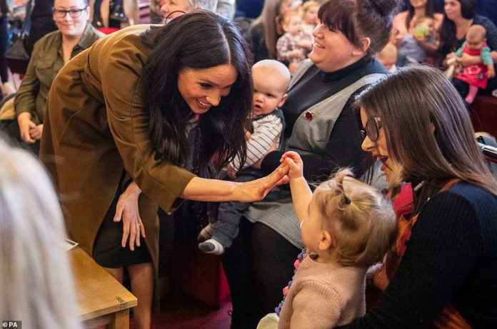 The Duchess of Sussex puts her hand out to a child from the family of a soldier in The Welsh Guards yesterday