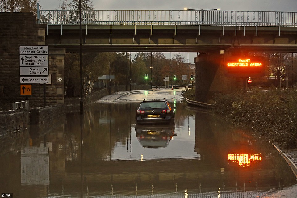 A car sits in floodwater near Meadowhall shopping centre in Sheffield today where people were forced to stay overnight