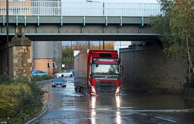 A lorry drives through floodwater near Meadowhall shopping centre in Sheffield today after the flooding chaos last night