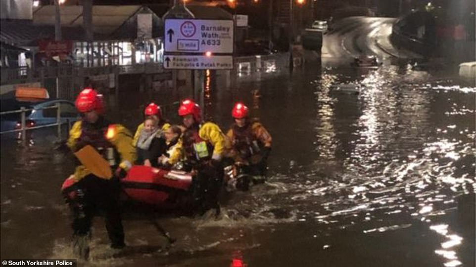 Firefighters rescue people in a boat from the Parkgate shopping centre in Rotherham last night following major flooding