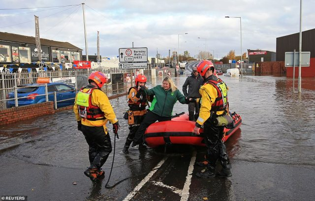 Rescuers help a woman get off an inflatable raft after ferrying her through floodwater in Rotherham this morning