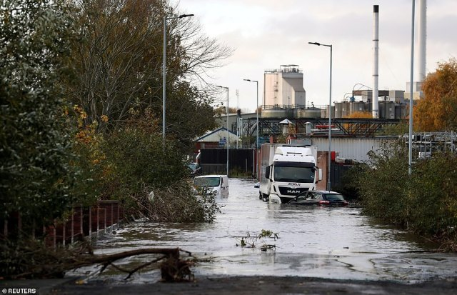 Vehicles sit in floodwater in Rotherham this morning after the town in South Yorkshire experienced intense rainfall overnight