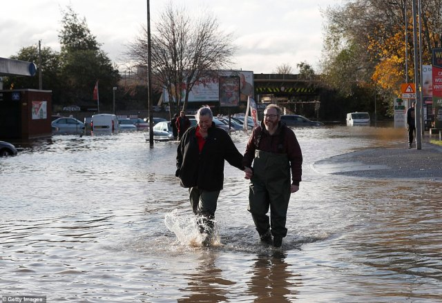 A couple wade through floodwater today in Rotherham, South Yorkshire, this morning after the River Don burst its banks