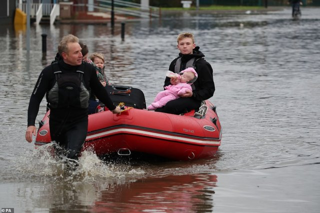 A young man feeds a child a bottle of milk as his father pulls an inflatable boat over floodwater in Doncaster this morning