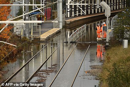 Workers inspect flooded rail tracks at Rotherham station today