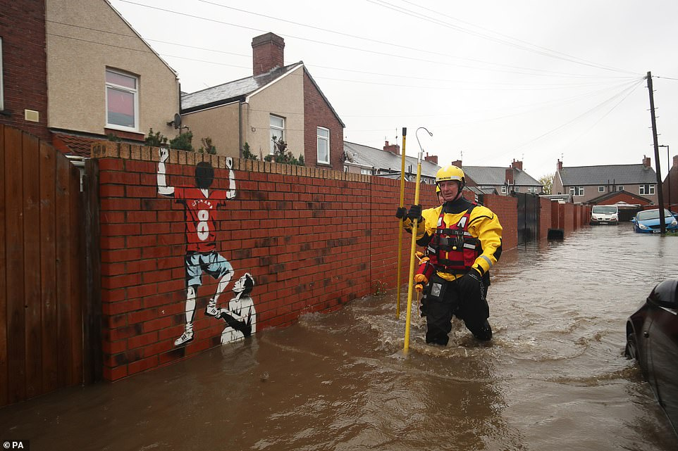 Fire and Rescue service members walk through flood water to rescue residents in Doncaster this afternoon