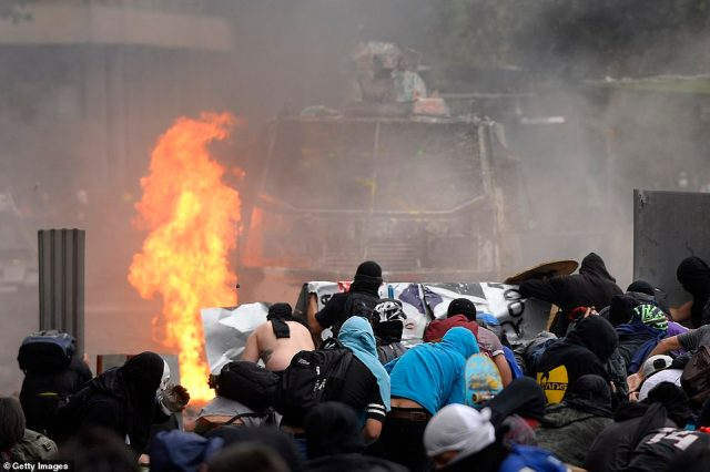 Chile's president, Sebastian Pinera, announced measures earlier this week to increase security and toughen sanctions for vandalism. Pictured:Demonstrators cover themselves from the riot police in Santiago as fires rage on the streets