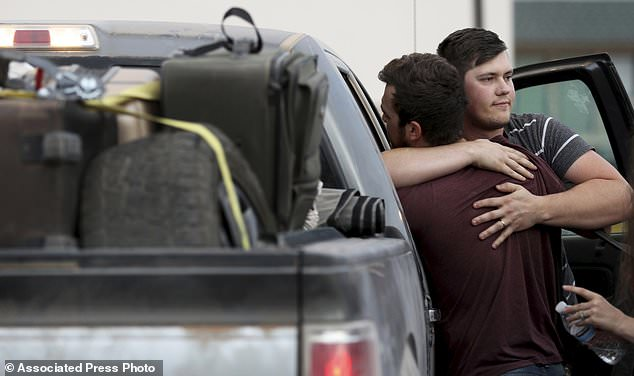 Cole Langford, left, and Hayden Spenct, of the Mormon colony of La Mora, Mexico, get hugged at a gas station rendezvous in Douglas, Arizona.