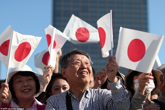 People were pictured smiling and waving Japanese national flags near the Imperial Palace before the royal parade. Meanwhile theKimigayo national anthem was played by the marching band on the Sunday