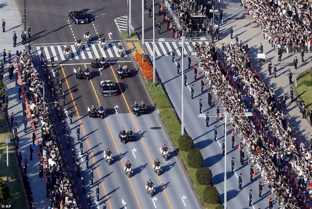 Crowds squeeze to get a close spot by the railings where they watchNaruhito, who studied at Oxford, drive past in the motorcade. It is thought that many Japanese natives were impressed by the royal couple openly conversing withPresident Donald Trump and first lady Melania Trump