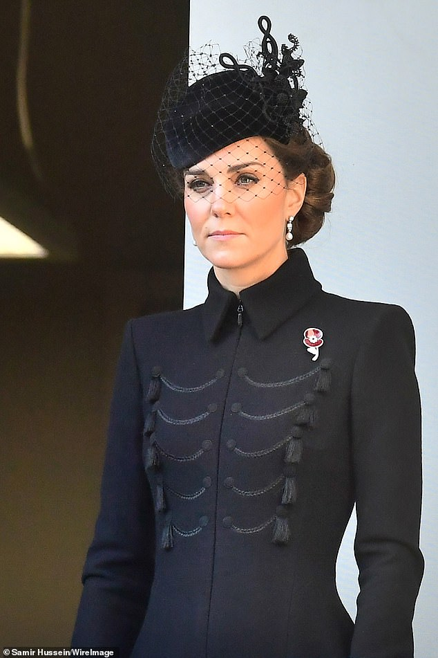 The Duchess of Cambridge, 37, both opted for a black coat and a hat as she stood on the balcony, watching Prince Charles, Prince William, and Prince Harry tie their wreaths to pay homage to the war dead