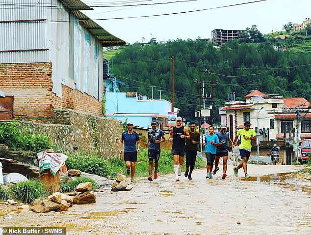 He jogs along a rain-soaked road in Nepal in a group during his global adventure and while he says the views were breathtaking, it was the people he met which was the 'best part'