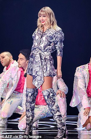 Center stage: Maintaining her quirky display, The Belong To Me hitmaker tied in her outerwear with a clingy bodysuit and high-heeled boots of the same pattern