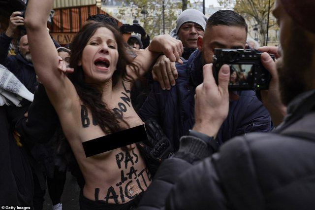 Thousands marched through Paris today in an anti-Islamophobia demonstration that has divided France's political class. A topless woman (pictured), who had 'we're not promoting secularism' written on her chest, also joined the protest, but appears to be from the feminist group Femen protesting for a secular society