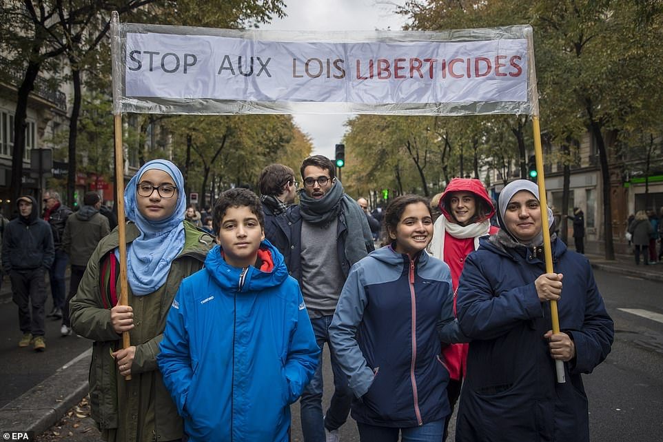A group of protesters hold a banner reading 'Stop to the liberticidal laws', as people and members of anti-racism associations gather to protest against Islamophobia at the Gare du Nord in Paris