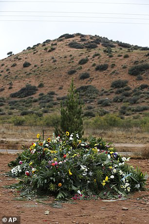 In the photo, the freshly excavated graves containing the remains of Rhonita Miller and four of his young children are covered with flowers a day after their burial.
