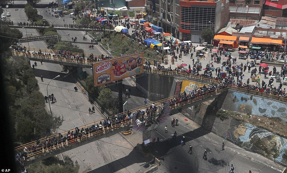 Supporters of now former Bolivian President Evo Morales stand on pedestrian bridges as they block a road that connects La Paz and El Alto