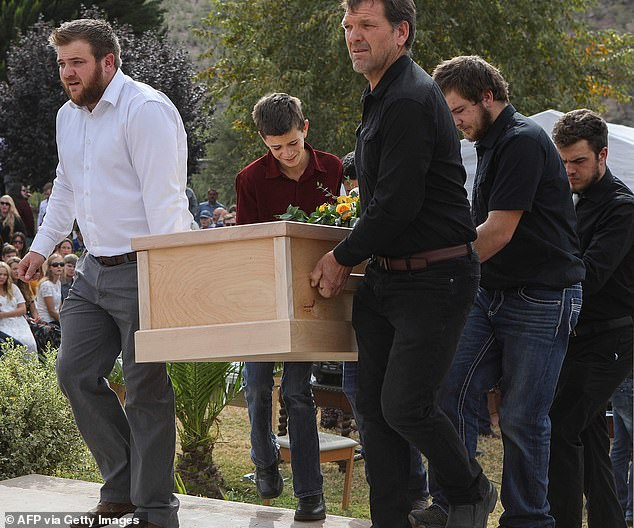 Devin (center in red shirt) helped carry a coffin during the funeral service last Thursday for his mother and two brothers