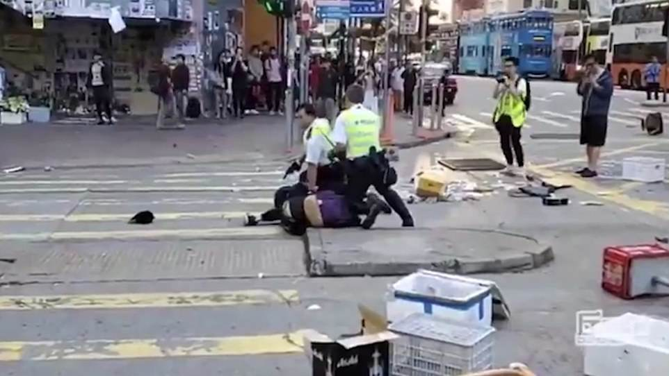 The police officers can be seen detaining the men on the ground, it is not clear from the footage whether the conscious man had been shot