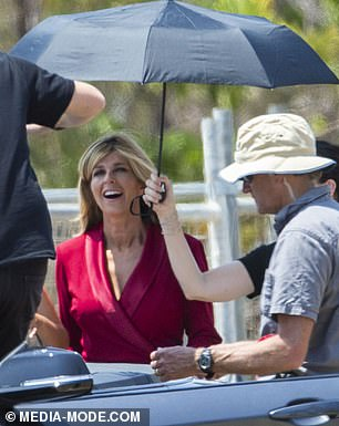 Being looked after: Kate was sheltered from the heat by an entourage who held a black parasol over her