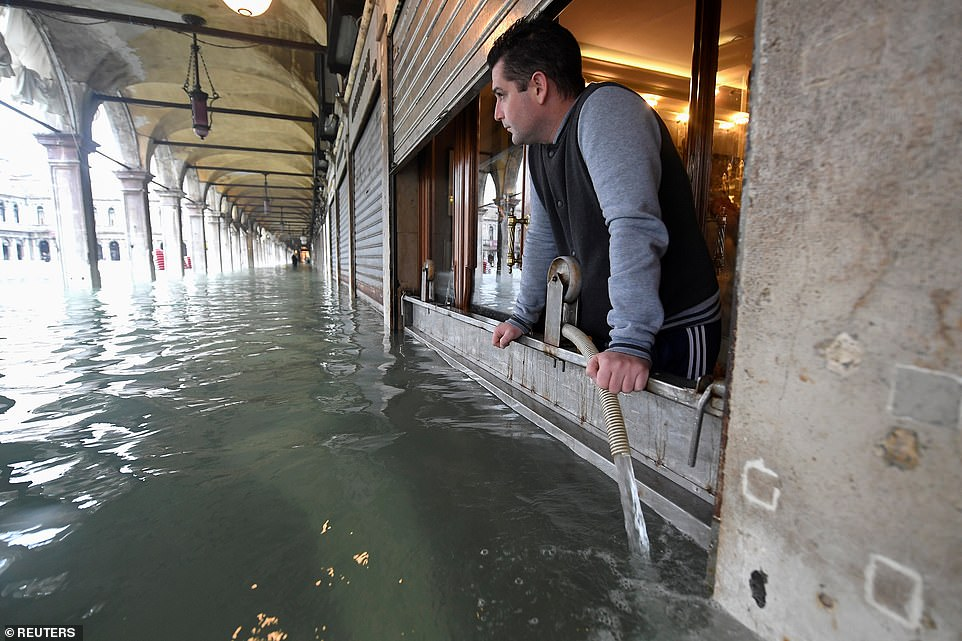 A man pumps water from a shop at the flooded St. Mark's Square, as the high tide reaches another peak today