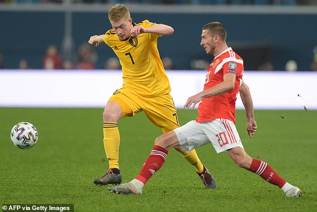 Kevin de Bruyne looks to push forward while being tracked by Russia's Alexey Ionov