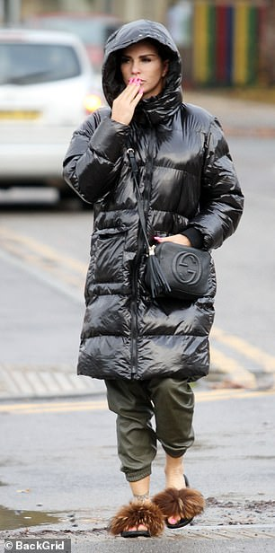 Casual: Katie was dressed for the grim weather on the outing, donning a black knee-length coat with her hood up