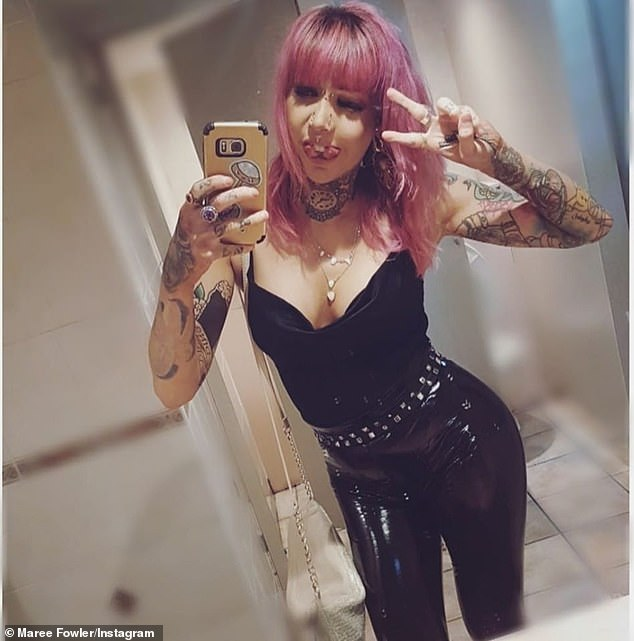 Ms Fowler has many piercings and tattoos and takes a selfie wearing a black top and skin-tight pants