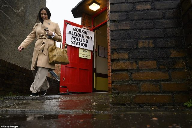 A woman exits a polling station in a wet and windy Birchgrove, Cardiff, this morning